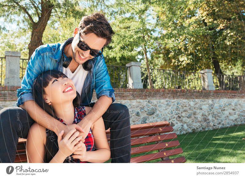 Junges glückliches Paar mit Smartphone im Park sitzend asiatisch schön Freund lässig Solarzelle Handy Chinese Mitteilung Verbindung Textfreiraum Frau