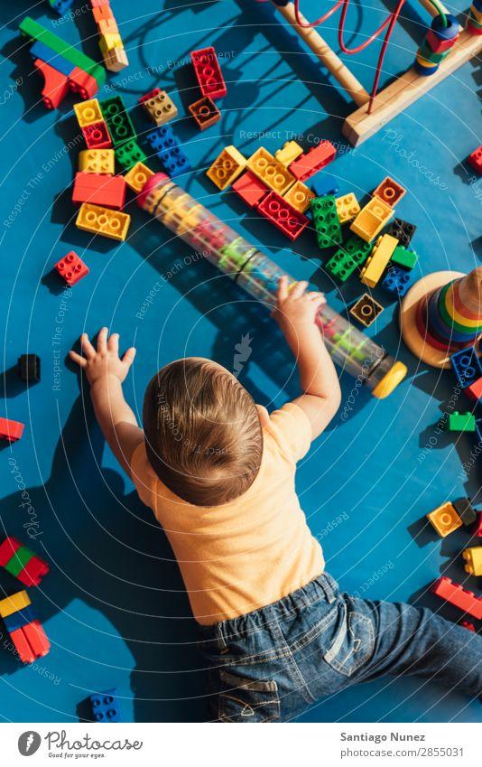 Frohes Baby beim Spielen mit Spielzeugblöcken. Kinderbetreuung Kindergarten Schule Kleinkind Junge klein Glück Fürsorge Etage niedlich Freude Vorschule Bildung