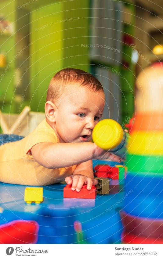 Glückliches Baby spielt im Kindergarten mit Spielzeugblöcken. Spielen Kinderbetreuung Schule Kleinkind Junge klein Fürsorge Etage niedlich Freude Vorschule