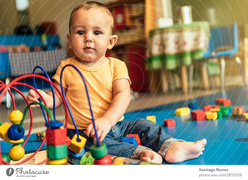 Frohes Baby beim Spielen mit Spielzeugblöcken. Kinderbetreuung Kindergarten Schule Kleinkind Junge klein LEGO Glück Fürsorge Etage niedlich Freude Vorschule