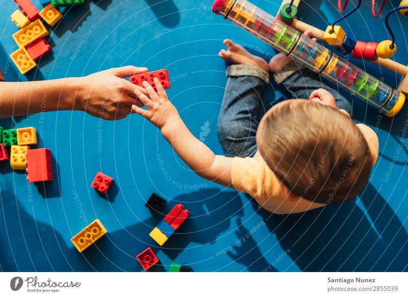 Frohes Baby beim Spielen mit Spielzeugblöcken. Kinderbetreuung Kindergarten Schule Mutter Lehrer Hilfsbereitschaft Mama Kleinkind Junge klein LEGO Glück
