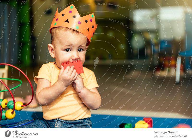 Frohes Baby beim Spielen mit Spielzeugblöcken. Kinderbetreuung Kindergarten Schule Krone König beißen Kleinkind Junge klein Glück Fürsorge Etage Porträt