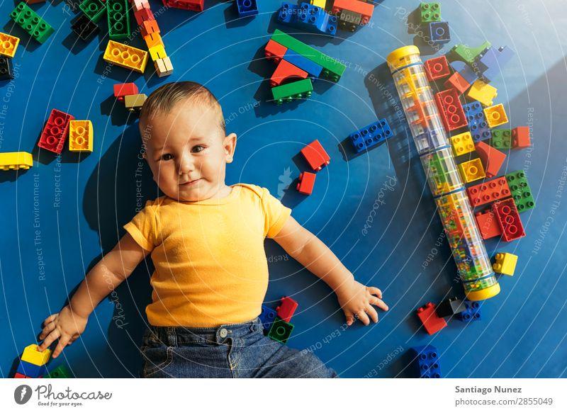 Frohes Baby beim Spielen mit Spielzeugblöcken. Kinderbetreuung Kindergarten Schule Kleinkind Junge klein Blöcke Glück Fürsorge Etage niedlich Freude Vorschule
