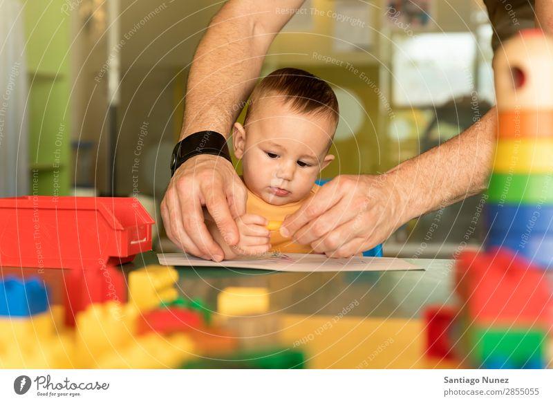 Kleinkind und Vater zeichnen auf einem Papier. Baby Spielen Kinderbetreuung Kindergarten Lehre Schule Papa Familie & Verwandtschaft lernen malen Spielzeug Farbe