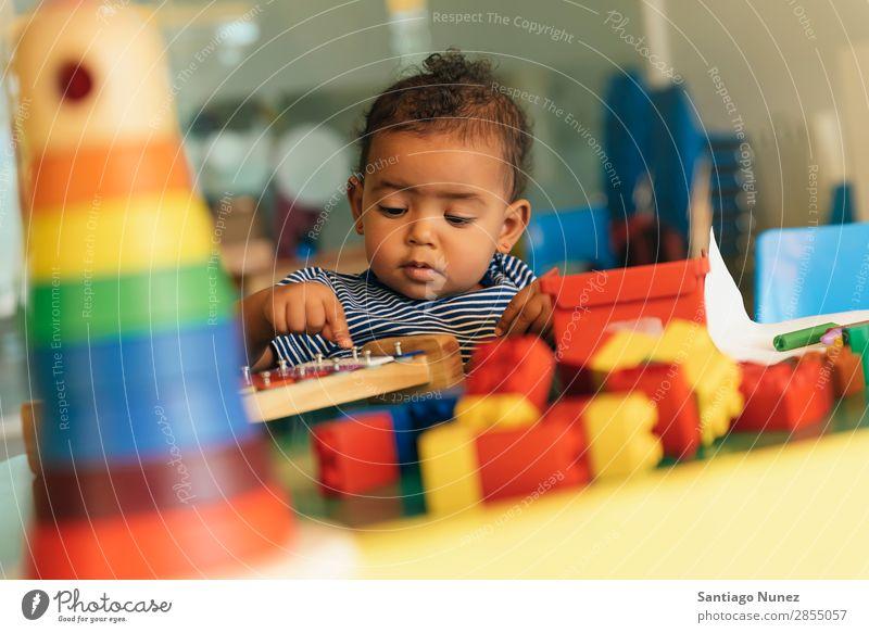 Frohes Baby beim Spielen mit Spielzeugblöcken. Kinderbetreuung Kindergarten Schule Kleinkind Mädchen klein Blöcke Glück Fürsorge niedlich Freude Vorschule