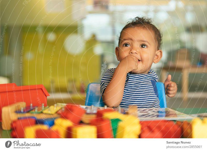 Frohes Baby beim Spielen mit Spielzeugblöcken. Kinderbetreuung Kindergarten Schule Kleinkind Mädchen klein Blöcke Lächeln Glück Fürsorge niedlich Freude
