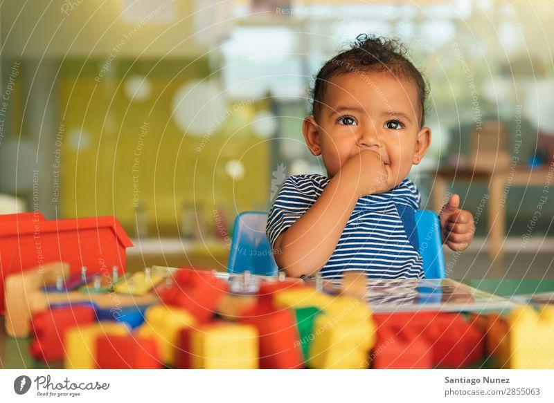 Frohes Baby beim Spielen mit Spielzeugblöcken. Kinderbetreuung Mulatte multiethnisch Kindergarten Porträt Schule Kleinkind Mädchen klein Blöcke Glück Fürsorge