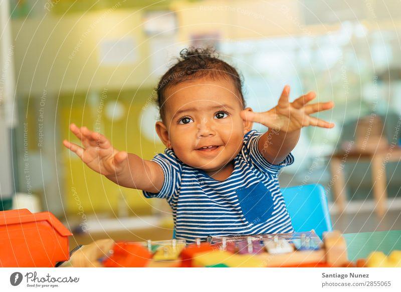 Frohes Baby beim Spielen mit Spielzeugblöcken. Kinderbetreuung Kindergarten Schule Kleinkind Mädchen klein Blöcke Lächeln Glück Fürsorge niedlich Umarmen