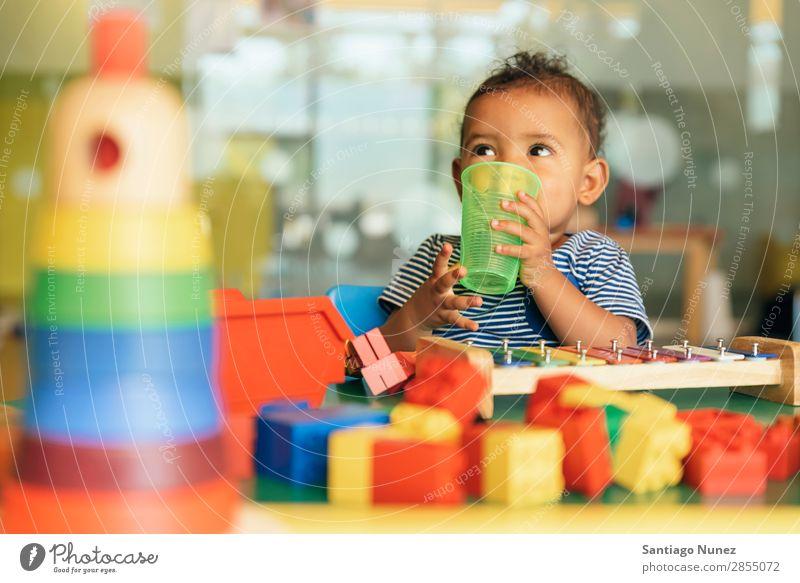 Frohes Baby, das Wasser trinkt und spielt. Spielen Kinderbetreuung Kindergarten Schule Spielzeug Kleinkind Mädchen klein Blöcke Glück Fürsorge Etage niedlich
