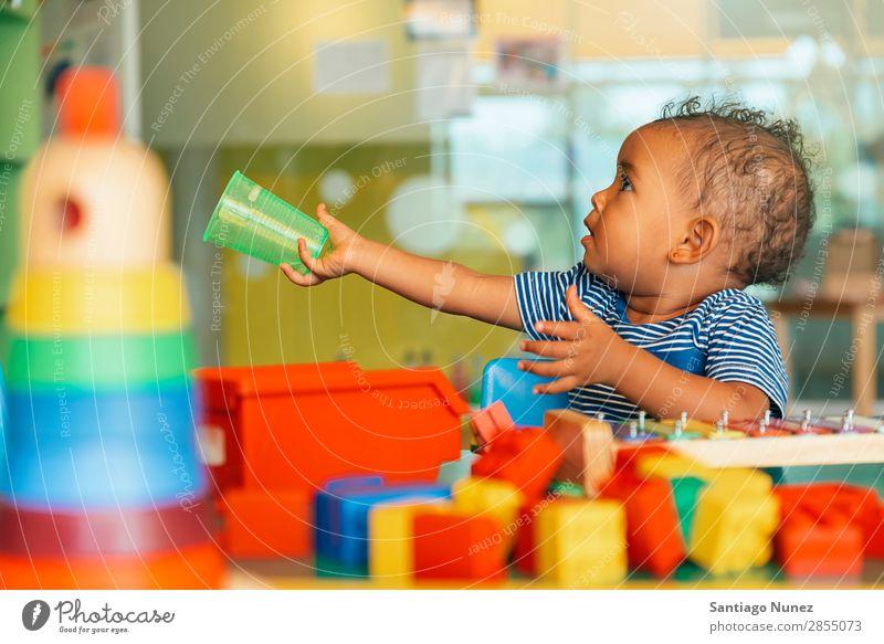 Das glückliche Baby will Wasser. Spielen Kinderbetreuung Kindergarten Schule Spielzeug Kleinkind Mädchen klein Blöcke Glück Fürsorge Etage niedlich Freude
