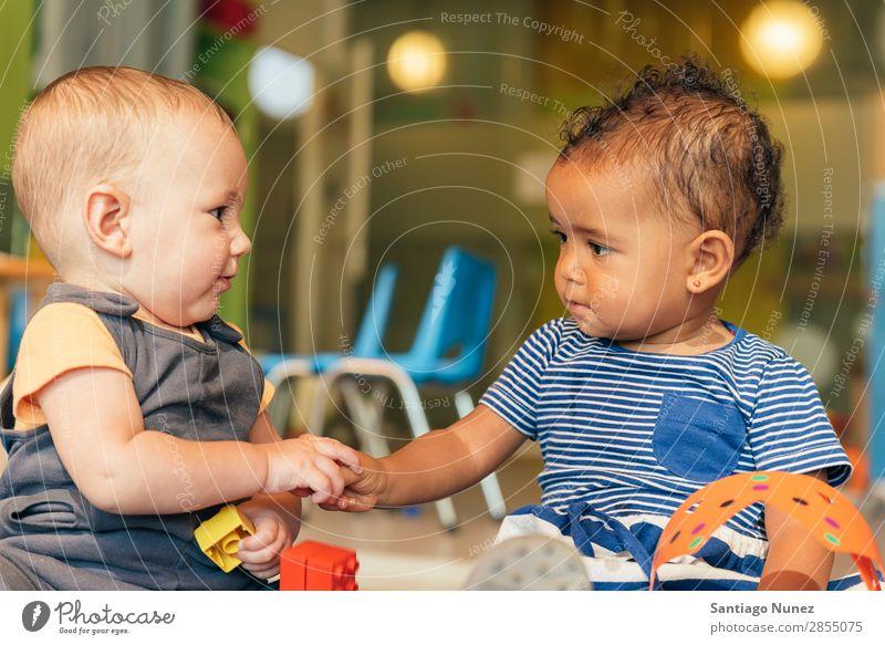 Babys spielen zusammen. Spielen Kind Kindergarten Tun 2 Freude Junge Kinderbetreuung Glück Mulatte multiethnisch Kaukasier heimwärts Kindheit Lifestyle Mensch