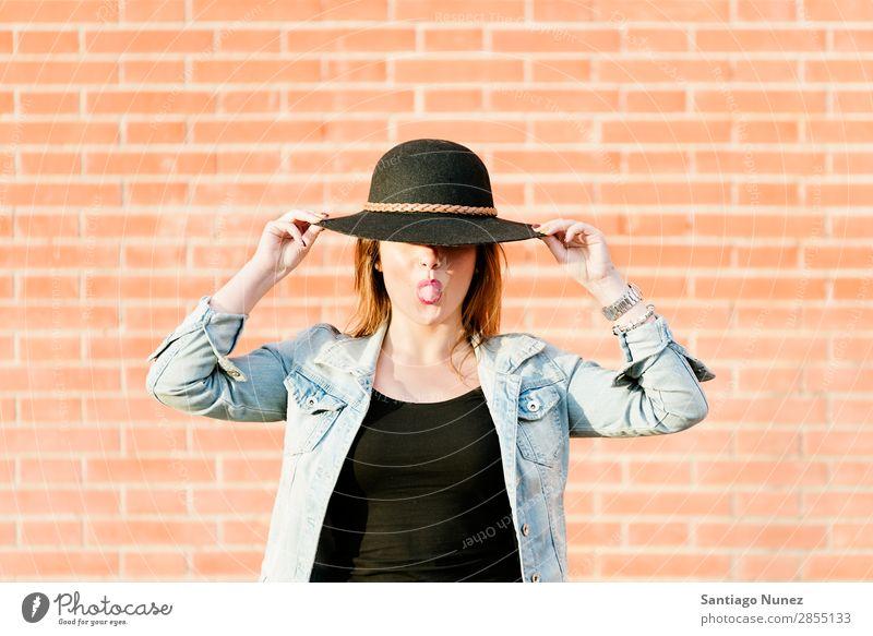 Blonder Hipster mit Strohhut auf orangem Ziegelgrund. Mode Wand Mädchen trendy Frau Jugendliche Schickimicki lässig Backstein Hintergrundbild Stil Porträt blond