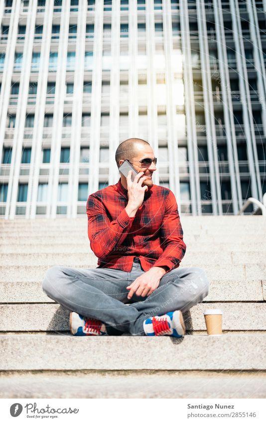 Junger Mann mit Handy in der Stadt. Mobile Telefon Schickimicki Lifestyle stehen Großstadt Gebäude Solarzelle PDA Mensch gutaussehend Stil Straße Kaffee