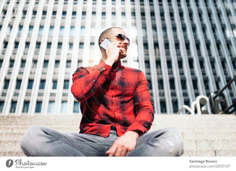 Junger Mann mit Handy in der Stadt. Mobile Telefon Schickimicki Lifestyle stehen Großstadt Gebäude Solarzelle PDA Mensch gutaussehend Stil Straße