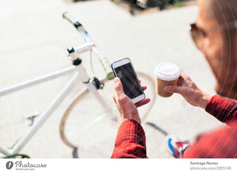 Junger Mann benutzt sein Handy auf der Straße. Mobile Porträt Glück Lächeln Telefon Schickimicki Lifestyle stehen benutzend Großstadt Solarzelle Stadt Mensch