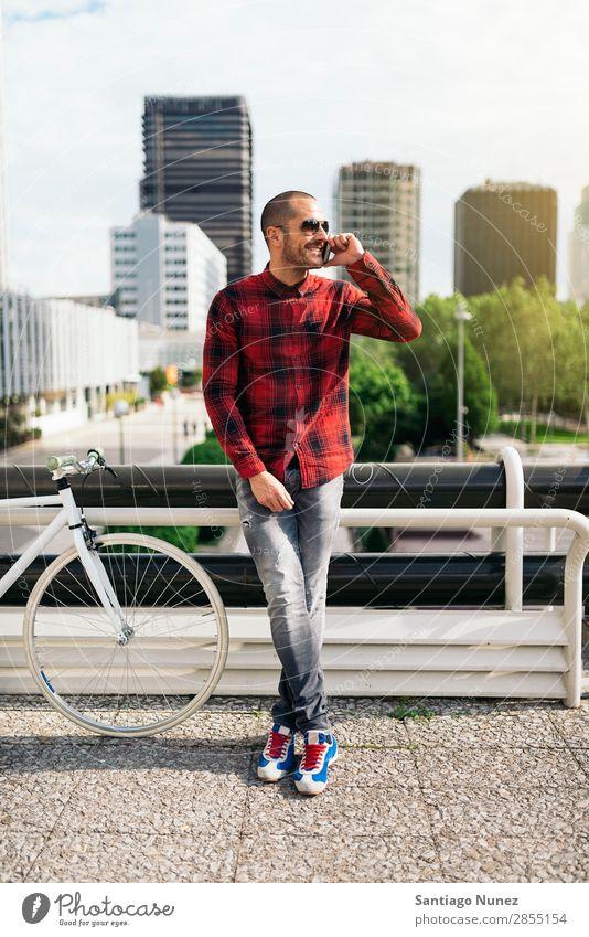 Junger Mann mit Handy und festem Fahrrad. Mobile Fixie Telefon Schickimicki Lifestyle stehen Fahrradfahren Großstadt Gebäude Solarzelle Stadt Mensch