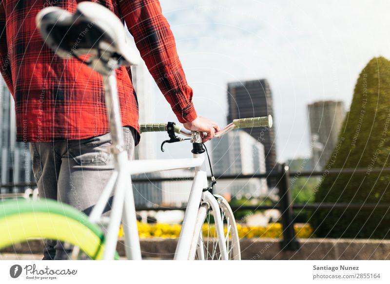 Junger Mann auf dem Fahrrad in der Stadt Fixie Schickimicki Lifestyle laufen Fahrradfahren Großstadt Solarzelle Mensch gutaussehend Stil Straße Porträt