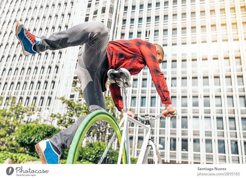 Gutaussehender junger Mann auf dem Fahrrad in der Stadt. Fixie Schickimicki Lifestyle Fahrradfahren Großstadt Solarzelle Mensch gutaussehend Stil Straße Porträt