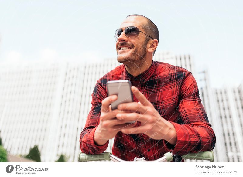 Junger Mann benutzt sein Handy auf der Straße. Mobile Porträt Glück Fahrrad Fixie Lächeln Telefon Schickimicki Lifestyle stehen benutzend Großstadt Solarzelle