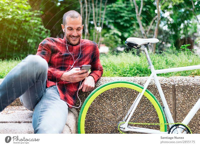 Junger Mann mit Mobiltelefon und Fahrrad mit festem Gang Mobile Fixie Telefon Hipster Lifestyle stehen Fahrradfahren Großstadt Gebäude Solarzelle Stadt Mensch