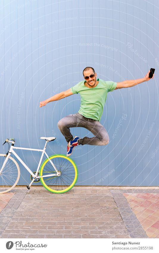 Outdoor-Porträt des schönen Springens. Mann springen Freude Lächeln Fahrrad Fixie Telefon Schickimicki Lifestyle stehen Fahrradfahren Großstadt Stadt Mensch