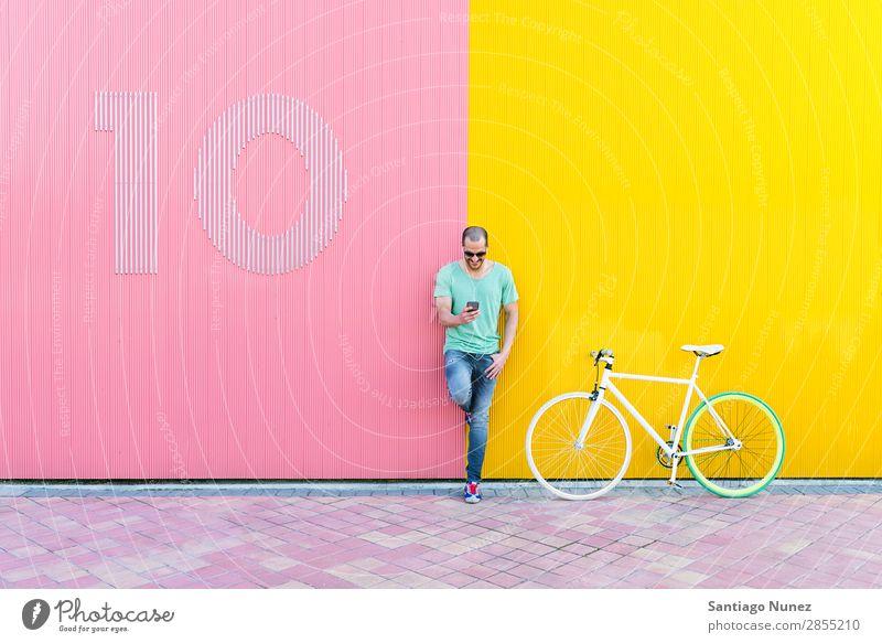 Gutaussehender junger Mann mit Handy und festem Fahrrad. Mobile Fixie Telefon Schickimicki Lifestyle stehen Fahrradfahren Großstadt Solarzelle Stadt Mensch