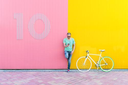 Gutaussehender junger Mann mit Handy und festem Fahrrad. Mobile Telefon Schickimicki Lifestyle stehen