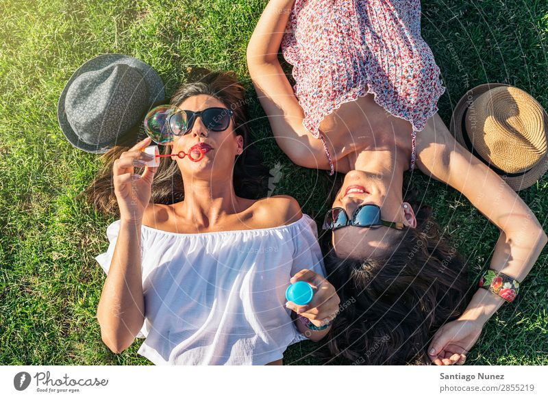 Fröhliche Mädchen beim Spaß im Park. Freundschaft Frau Glück Luftballon hübsch Fröhlichkeit Luftblase Seife schön Freude Blase Lifestyle Mensch Gras Sommer