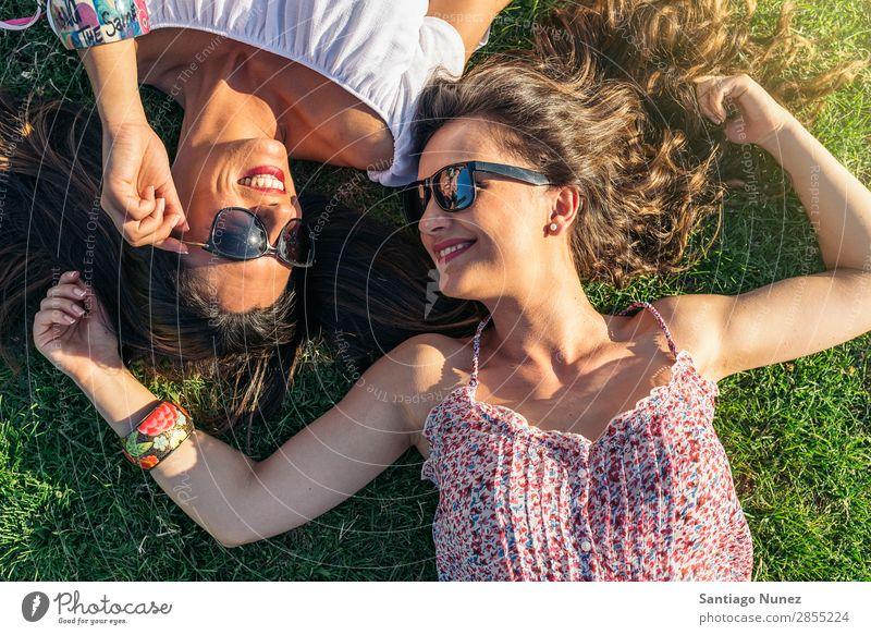 Fröhliche Mädchen beim Spaß im Park. Freundschaft Frau Glück hübsch lügen Fröhlichkeit schön Freude Lifestyle Mensch Gras Sommer Außenaufnahme Party Jugendliche