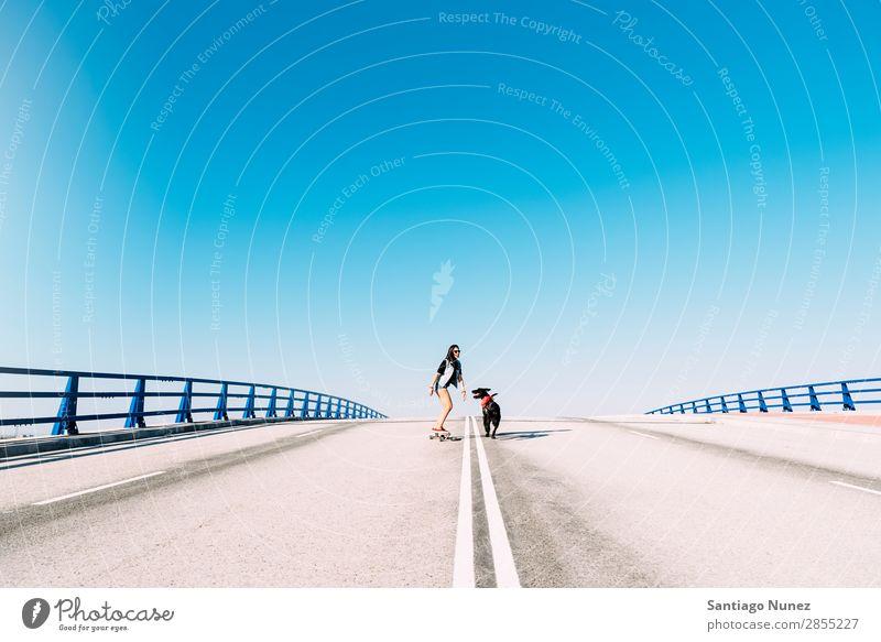 Schöne junge Skaterin, die mit ihrem Hund spielt. Mädchen Frau Haustier Besitzer Schlittschuhlaufen Stadt Jugendliche Sport Skateboarding Longboard Reiten