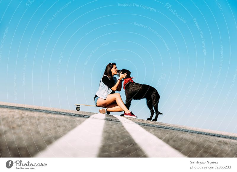 Schöner junger Mann, der ihren Hund liebt. Mädchen Frau Haustier Besitzer Schlittschuhlaufen Stadt Jugendliche Sport Skateboarding Longboard Reiten