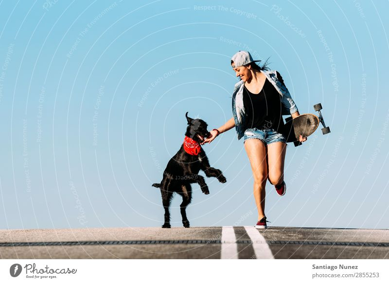 Ein wunderschöner junger Mann spielt mit ihrem Hund. Mädchen Frau Haustier Besitzer Schlittschuhlaufen Stadt Jugendliche Sport Skateboarding Longboard Reiten