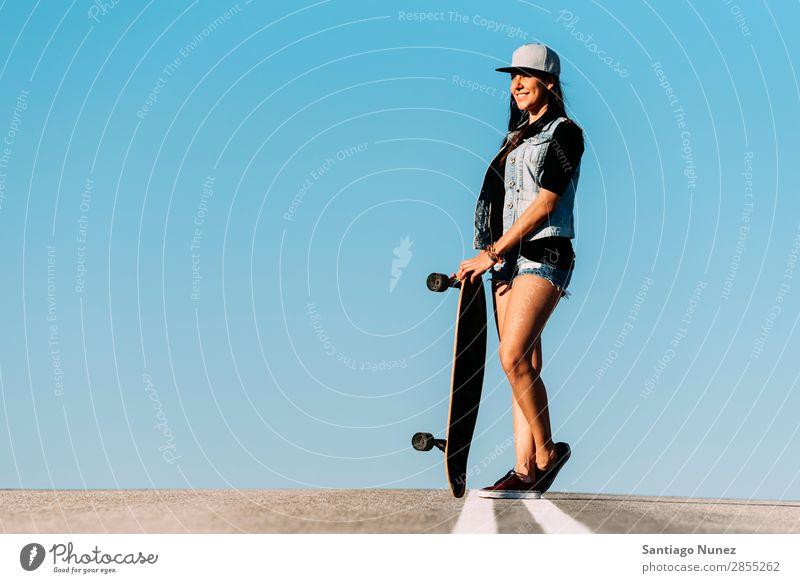 Schöne Skaterin, die mit ihrem Longboard posiert. Mädchen Frau Schlittschuhlaufen Stadt Jugendliche Sport Skateboarding Stil Reiten Schlittschuhe Glück Lächeln