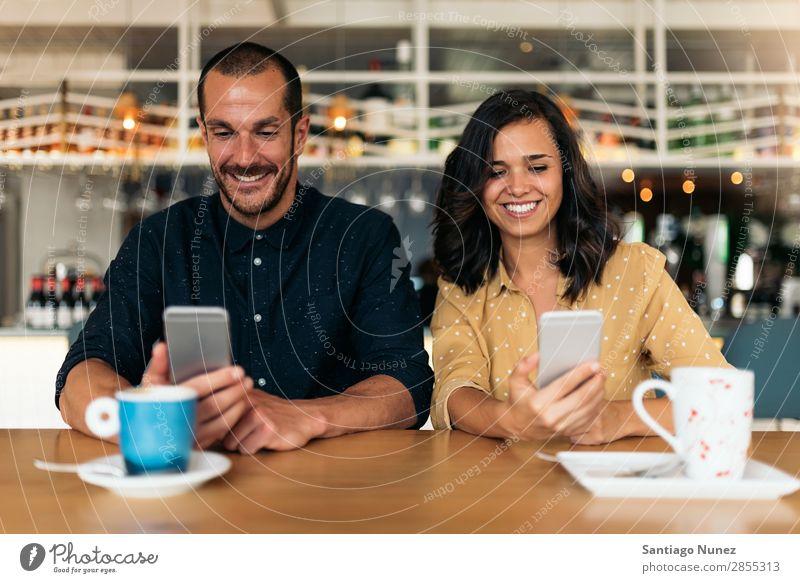 Glückliche Freunde, die das Handy benutzen. Frau Café Kaffee Mann Telefon Paar Mobile Lächeln schön Lifestyle Datteln Freundschaft Liebe Freude Bar Tisch