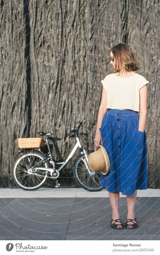 Junges sexy blondes Mädchen steht in der Nähe des Fahrrads. Erwachsene Hintergrundbild Tasche Korb schön Beautyfotografie blau braun Kaukasier Großstadt