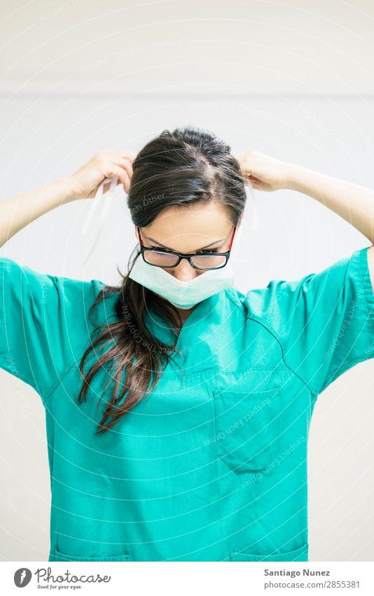 Die Krankenschwester arbeitet und setzt ihre medizinische Maske auf. blau Fürsorge Klinik überdeckt Arzt Gerät Frau grün Gesundheit Krankenhaus Mensch