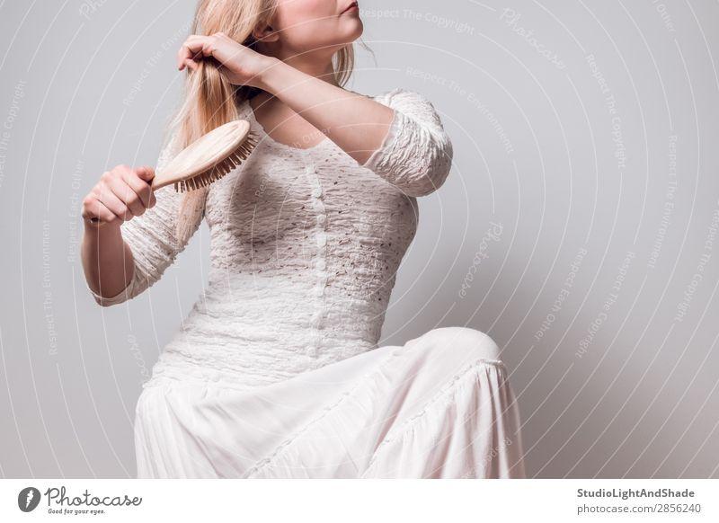 Dame in Weiß, die ihr blondes Haar bürstet. Lifestyle elegant Stil schön Körper Haare & Frisuren Gesundheitswesen Mensch feminin Frau Erwachsene Arme Hand Mode