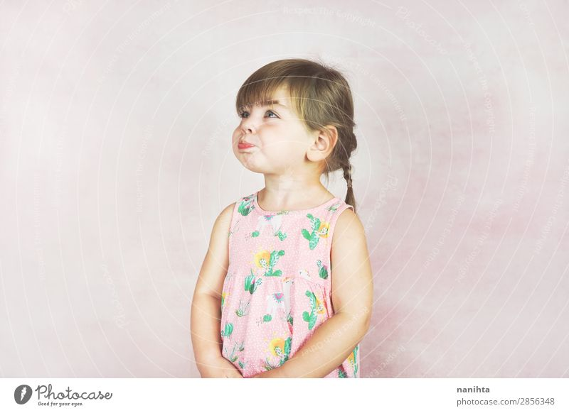 Junges kleines und lustiges Mädchen in einer Studioaufnahme Lifestyle Freude Gesicht Leben Kind Mensch feminin Kleinkind Kindheit 1 1-3 Jahre Kleid blond