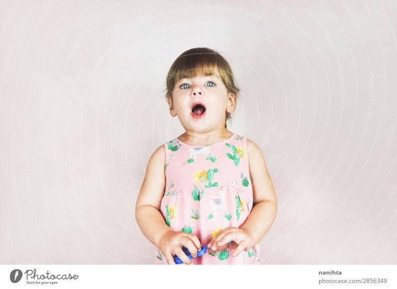 Junges kleines und lustiges Mädchen in einer Studioaufnahme Lifestyle Stil Freude Gesicht Leben Kind Mensch feminin Kleinkind Kindheit 1 1-3 Jahre Kleid blond