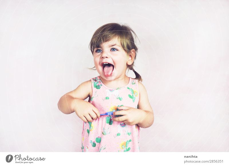 Junges kleines und lustiges Mädchen in einer Studioaufnahme Lifestyle Freude Glück Gesicht Leben Kind Mensch feminin Kleinkind Kindheit 1 1-3 Jahre Kleid blond