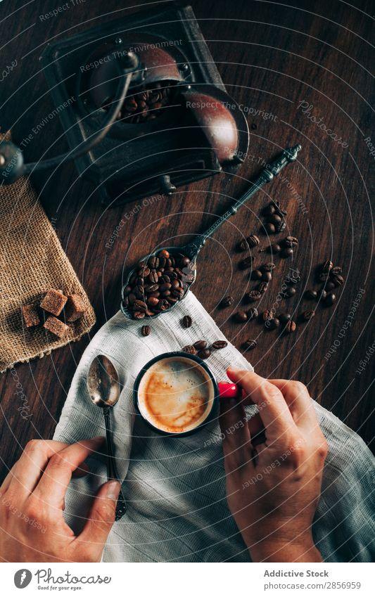 Die Nahaufnahme der Hände nimmt eine Tasse Espresso. Kaffee schwarz frisch stark Bohnen Kaffeebohnen Kaffeemühle Antiquität alt Zucker Würfel braun Serviette