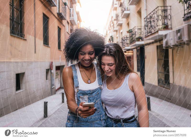 Schöne Frauen, die ein Handy auf der Straße benutzen. Freundschaft Afro-Look Jugendliche Glück Sommer Mensch Freude Mobile PDA Telefon Solarzelle benutzend