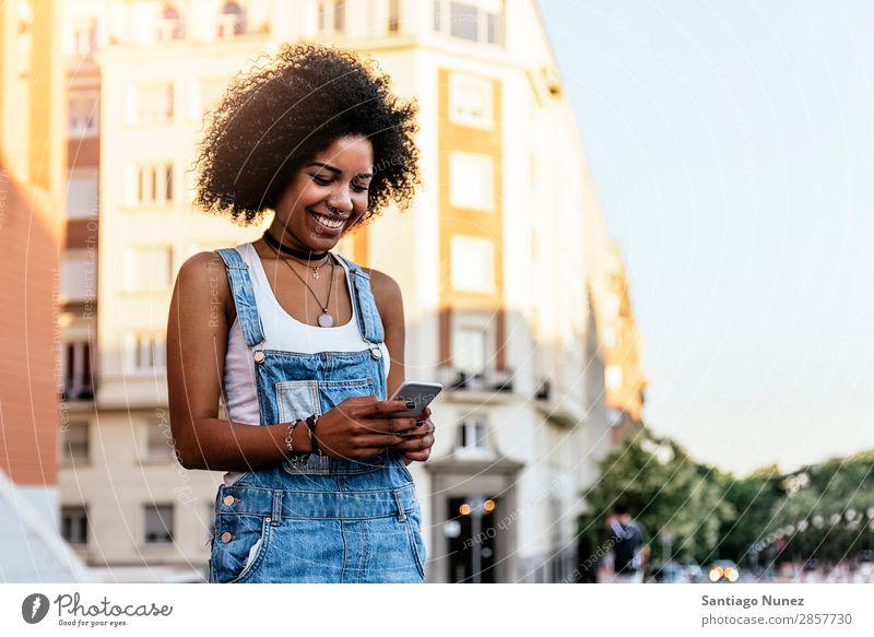 Schöne Frau mit Handy auf der Straße. Telefon schwarz Afrikanisch Mobile PDA Texten Mitteilung Afro-Look Mensch Porträt Großstadt Jugendliche Mädchen Amerikaner
