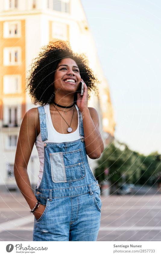 Schöne Frau mit Handy auf der Straße. Telefon schwarz Afrikanisch Mobile PDA Sprechen Afro-Look Mensch Porträt Großstadt Jugendliche Mädchen Amerikaner Lächeln