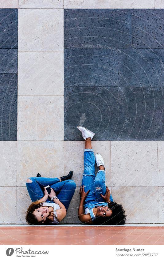 Schöne Frauen haben Spaß auf der Straße. Freundschaft Jugendliche Glück Sommer Mensch Freude Mobile PDA Telefon Solarzelle benutzend Mitteilung Texten Mädchen