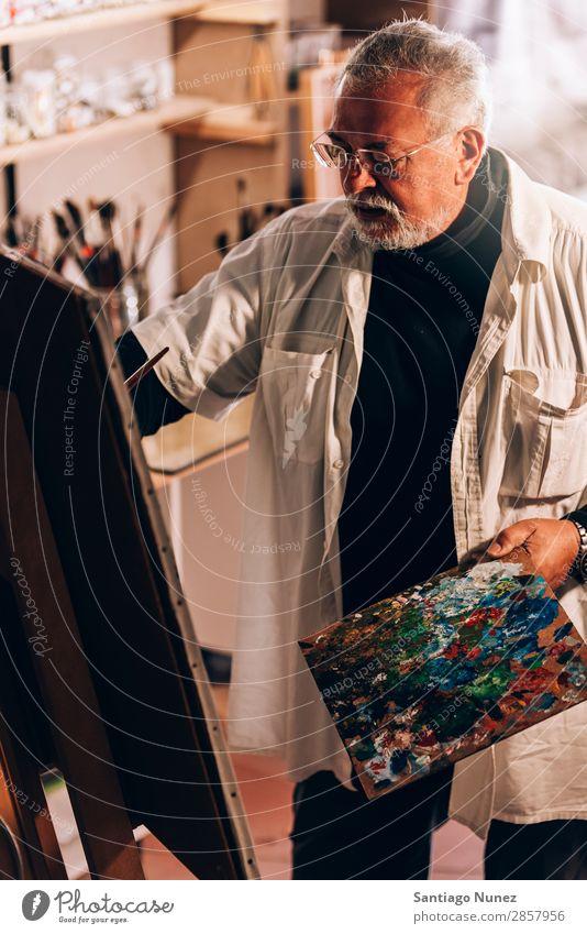 Alter Mann Künstler beim Malen von Ölen in seinem Atelier. Erwachsene Vollbart Maler konzentriert Gemälde Pinsel Bürste Staffelei Leinwand Konzentration