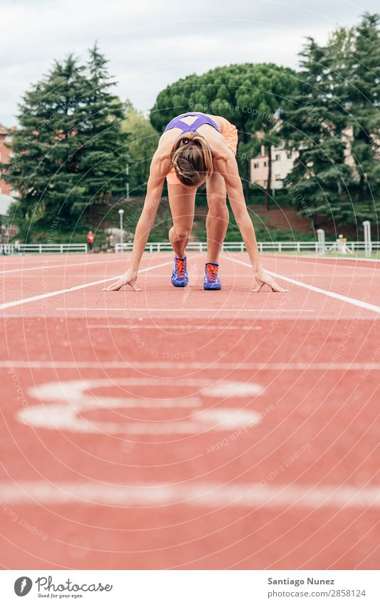 Frau macht sich bereit, mit dem Laufen zu beginnen. Athlet Leichtathletik schwarz Block Blöcke Bekleidung selbstbewußt Textfreiraum üben Feld bekommend