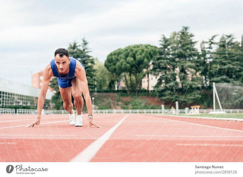 Mann macht sich bereit, mit dem Betrieb zu beginnen. Athlet Leichtathletik schwarz Block Blöcke Bekleidung selbstbewußt Textfreiraum üben Feld bekommend
