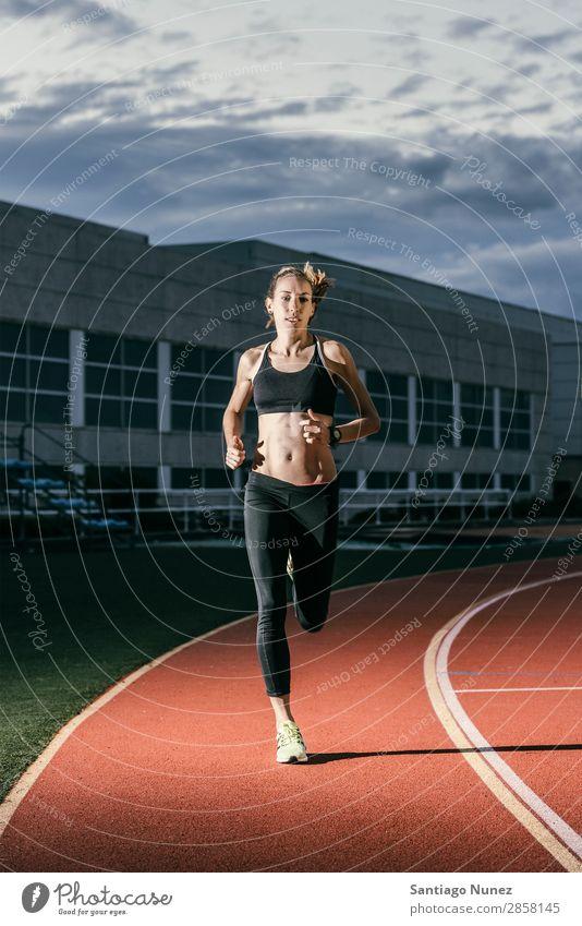 Attraktive Frau Leichtathletin, die auf der Strecke läuft. Aktion Athlet Athletik attraktiv kakuzasisch Herausforderung Konkurrenz selbstbewußt Tatkraft üben