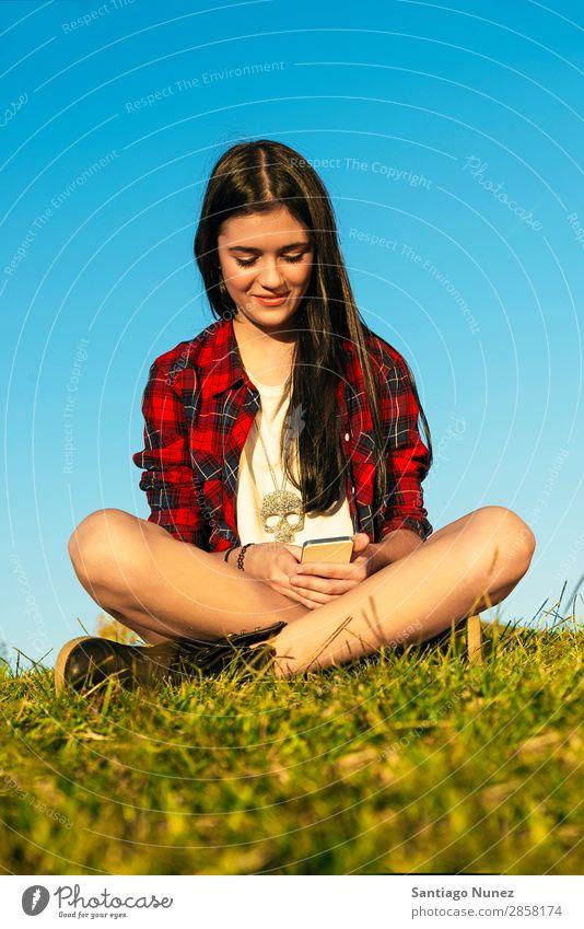 Fröhliches Teenager-Mädchen mit Handy im Park Jugendliche Mobile Mitteilung Amerikaner attraktiv schön Halterung Kaukasier Solarzelle Kommunikation Frau